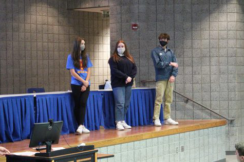 Luke Hamilton (12), Hailey Prasopoulos (12) 和 Marissa Haberling (10) listen to Ava Orueta (12) while she gives a speech. They were there to help answer questions at the end of the meeting.