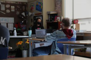 A student watches Mrs. Rokita teach virtually while guidance counselor Mrs. Rogers substitutes. Rogers had to fill in the place of the teacher in order to maintain adult supervision. Photo 通过: Jordan Znosko